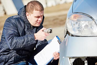 Insurance agent photographing car damage for claim form