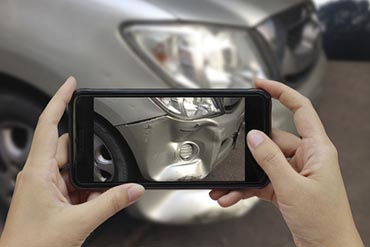Hand holding smart phone take a photo at The scene of a car cras